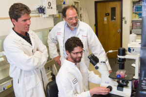 a color photo of three CSU researchers in the lab, discussing tuberculosis research
