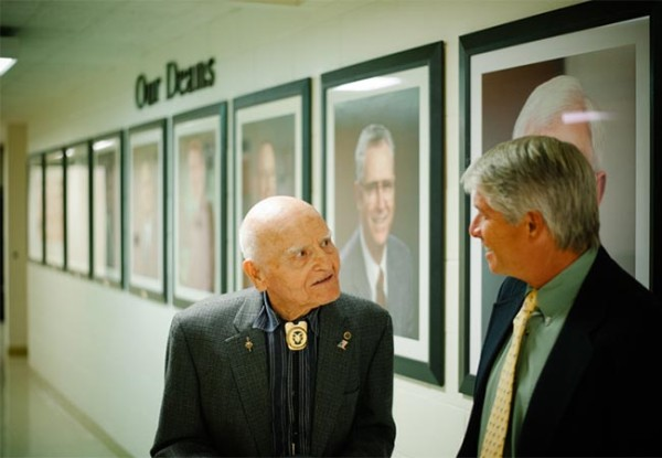 two men in hallway with portraits of deans