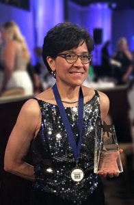 woman in sparkly top holding an award