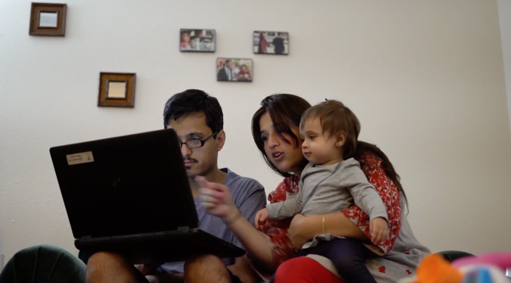 man holding laptop with woman and child