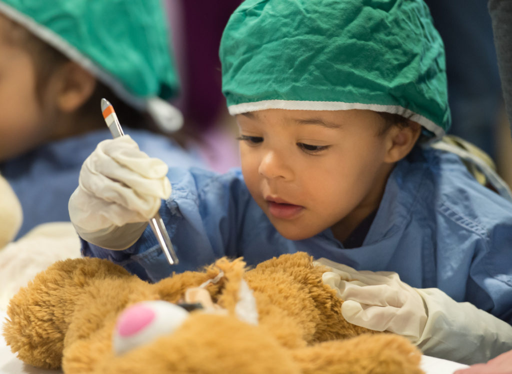 child in surgical cap holding tweezers over a stuffed bear