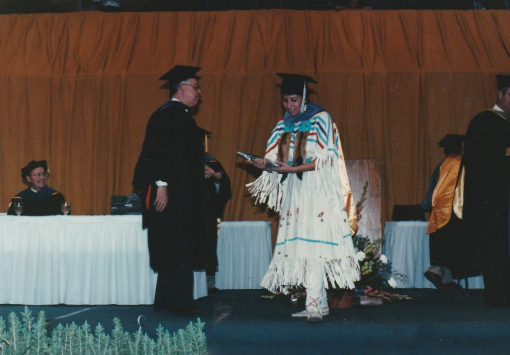 Woman in buckskin dress receiving diploma from man in graduation robes