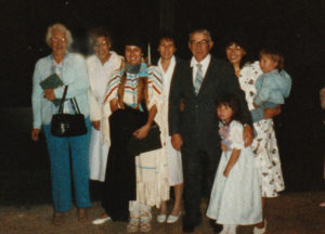 Family photo of 8 people including Ethel Connelly in a buckskin dress