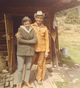 woman in a green coat and man in a leather Western suit in front of a cabin