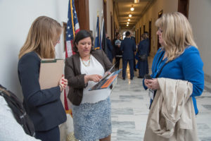 three woman standing in the hallway of the US Congress
