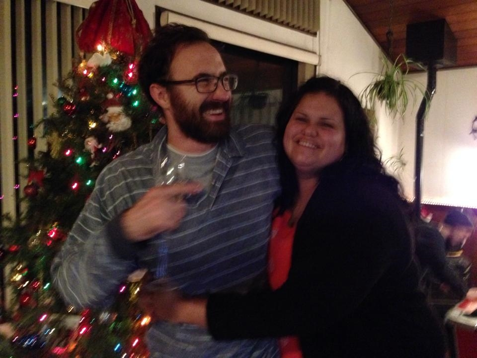 Aletta Kosakewich hugging husband in front of Christmas tree