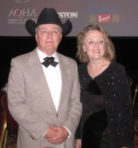 man in cowboy hat and woman in sparkly black dress