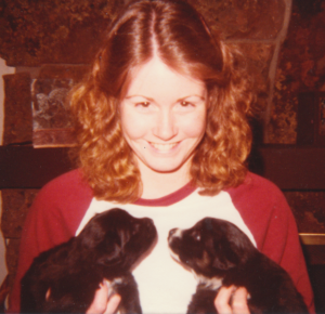 smiling girl holding two puppies
