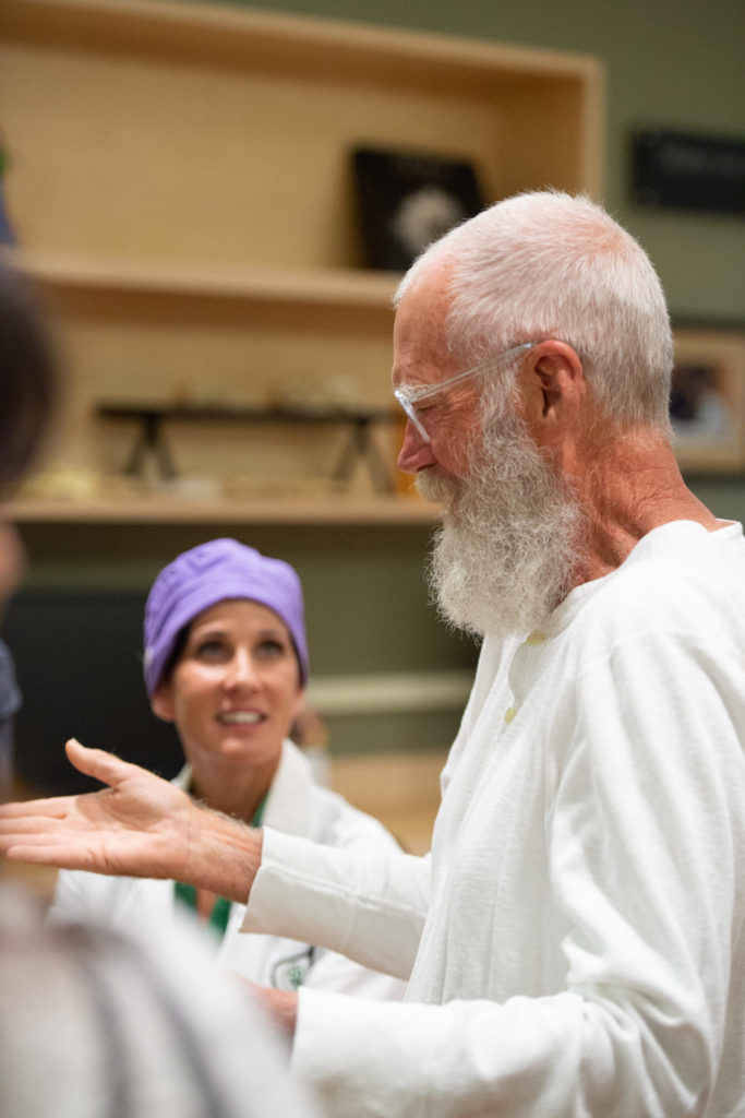 David Letterman, white shirt, and Dr. Nicole Ehrhart, purple surgical cap