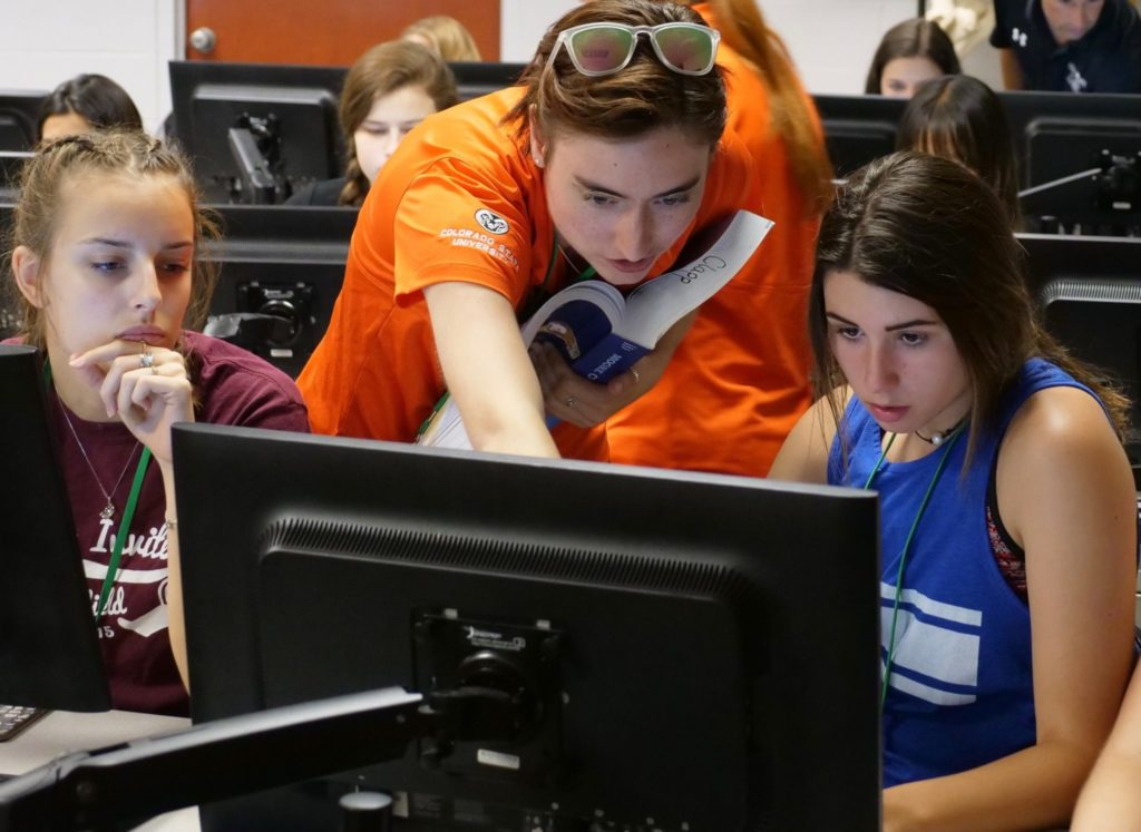 Katie Brown, biomedical sciences student, showing high school students something on a computer at Anatomy Camp