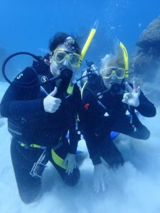 Hanah Georges (left) scuba diving the Great Barrier Reef.