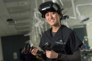 graduate student in black scrubs wears virtual anatomy goggles