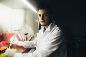 white male student in lab coat works in lab