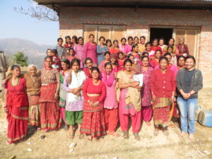 Nepali women and children smile for a group photos in front of a brown house