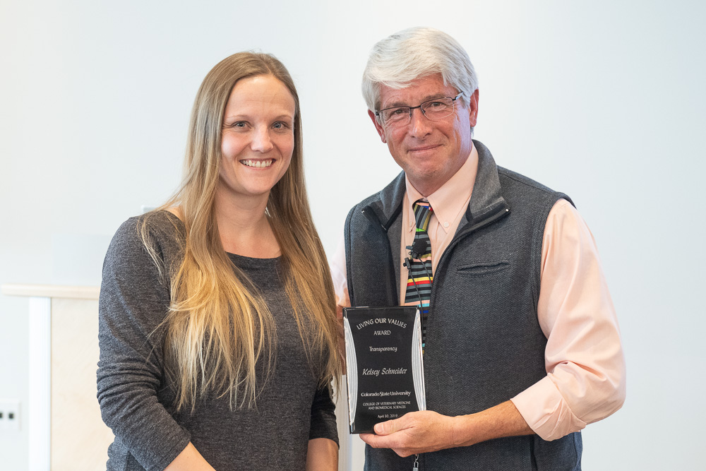Dean Stetter (right) presents Kelsey Schneider (left) with the Transparency Award.