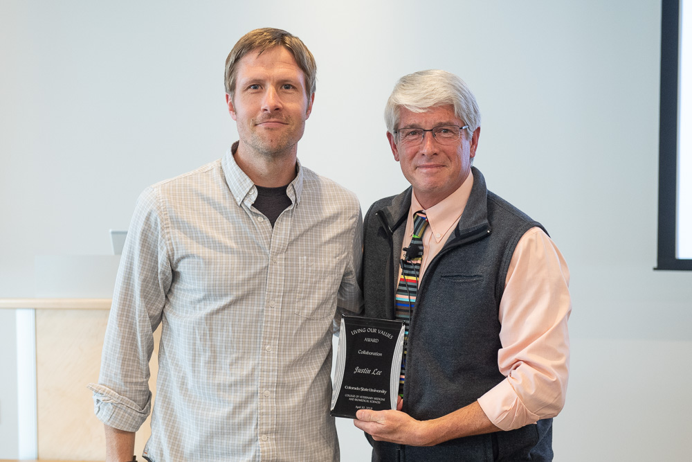 Justin Lee is presented with the Collaboration Living Our Values award by Dean Mark Stetter