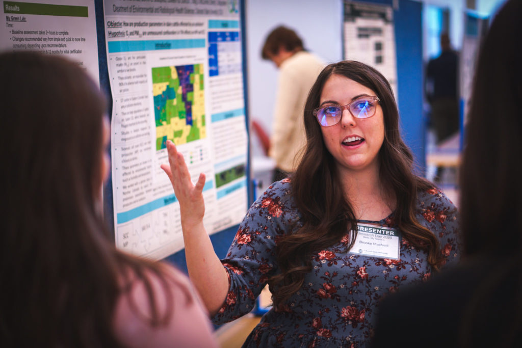 student describing her poster