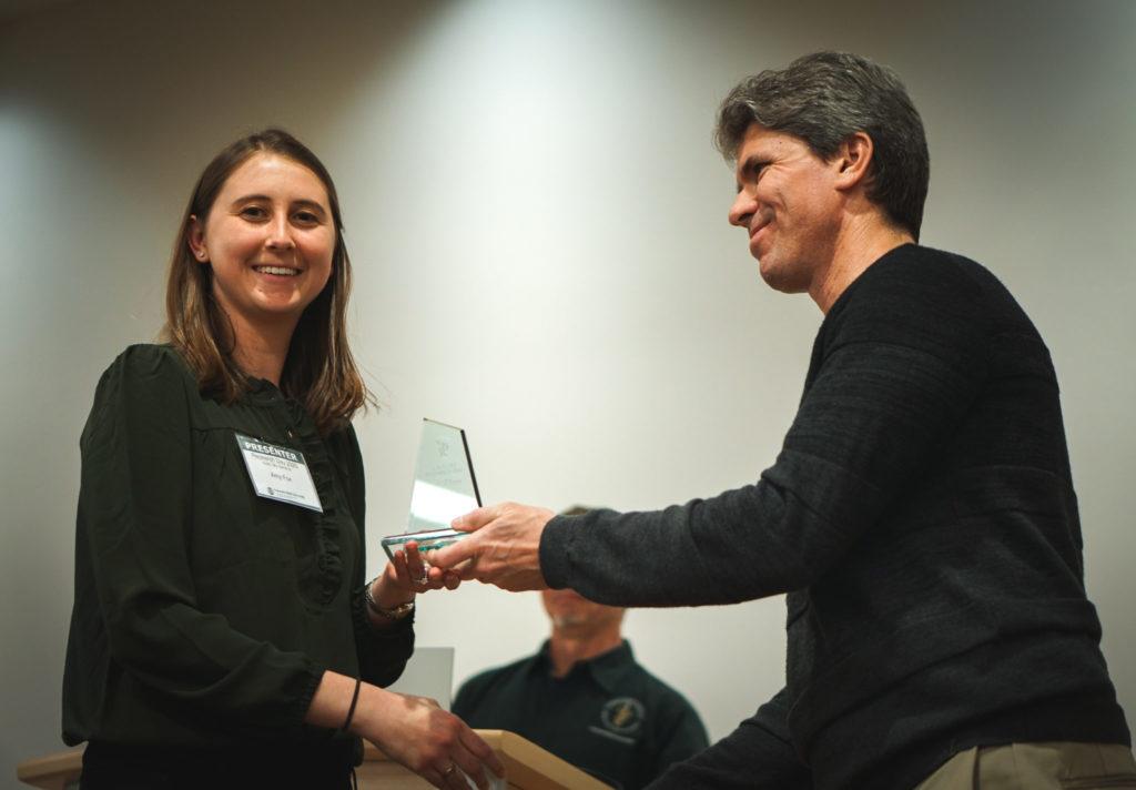 Amy Fox receiving award from Adam Chicco