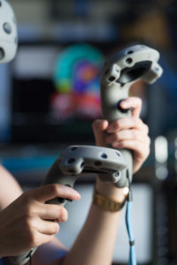 A student holding controllers for virtual reality