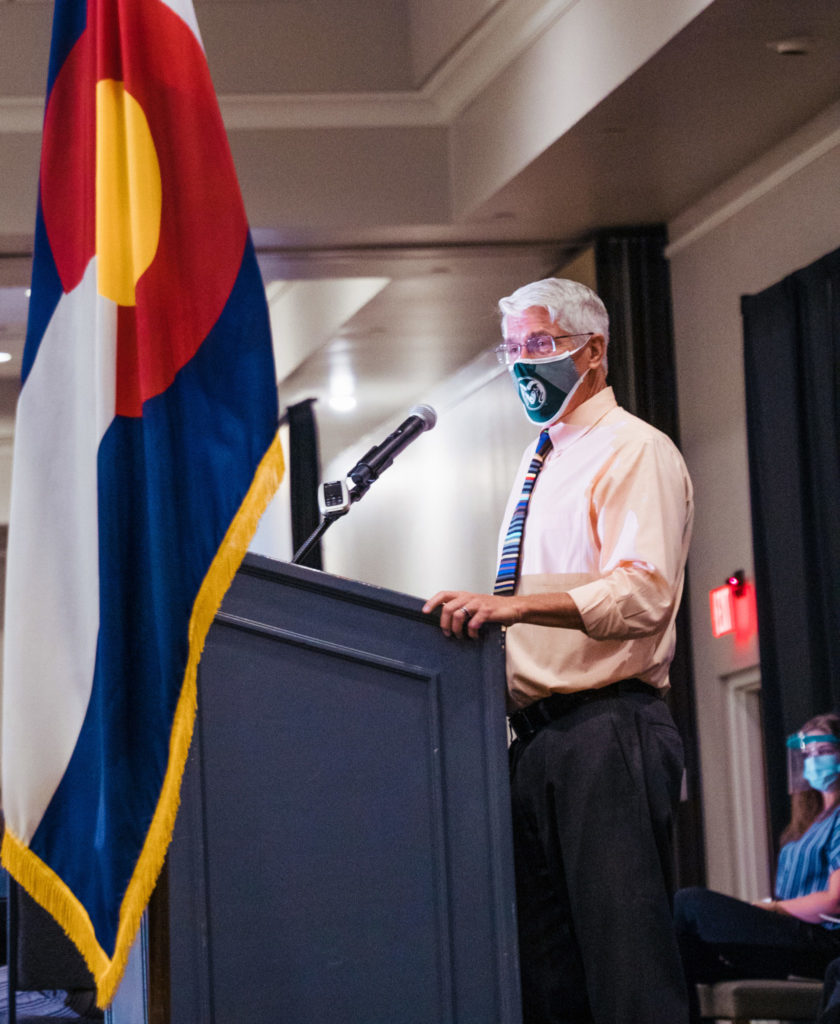 Dr. Mark Stetter, at a podium, wearing a mask
