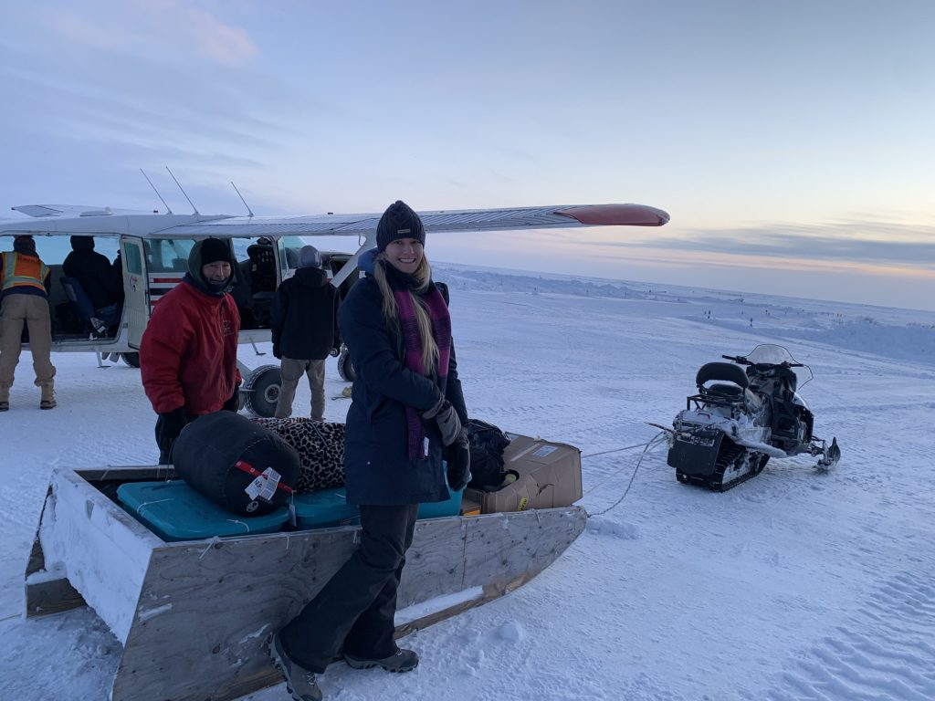 Amy Downey in front of a bush plane and snow sled