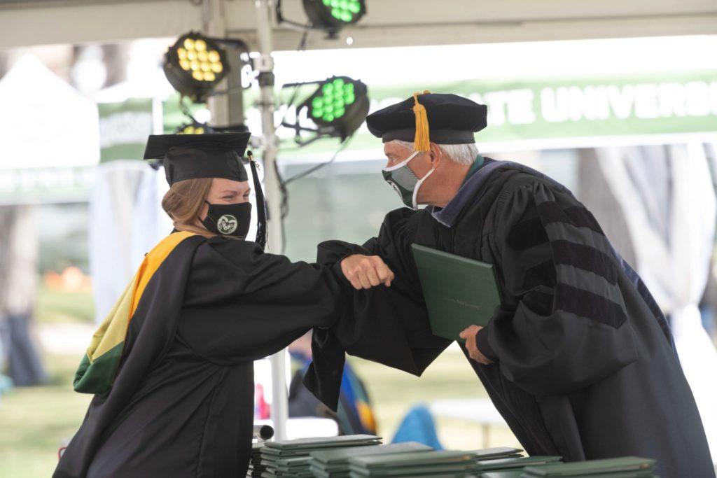 Dean Stetter handing a woman her diploma