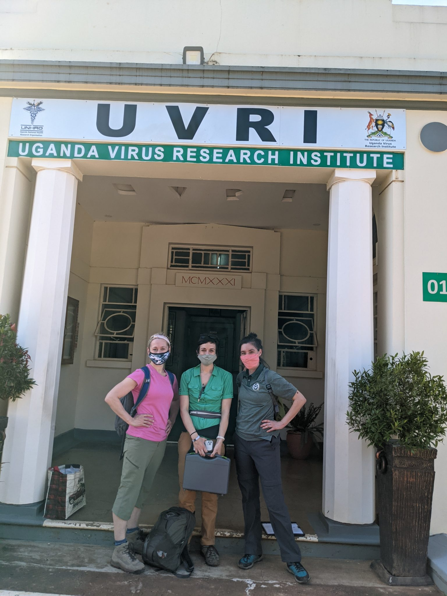 three scientists stand outside virus research institute